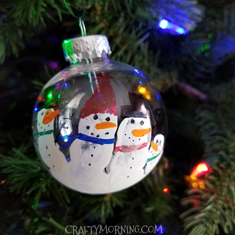 Start by painting your child's hand with white paint and having them grab  the clear ornament. Let dry then decorate with paint and sharpies. - Handprint Snowman Ornament Keepsake - Crafty Morning